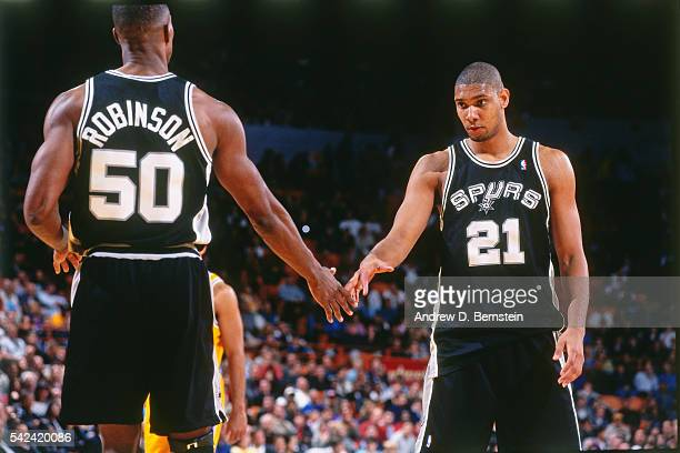 Tim Duncan of the San Antonio Spurs shakes hands with David Robinson of the San Antonio Spurs during the game against the Los Angeles Lakers on March...