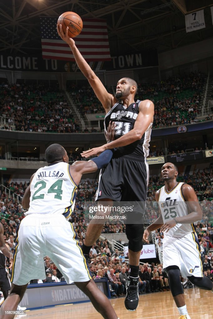 Tim Duncan #21 of the San Antonio Spurs shoots a layup against Paul Millsap #24 and Al Jefferson #25 of the Utah Jazz at Energy Solutions Arena on December 12, 2012 in Salt Lake City, Utah.