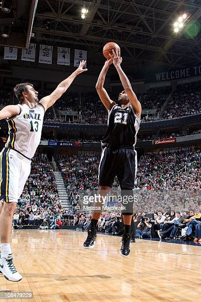 Tim Duncan of the San Antonio Spurs shoots over Mehmet Okur of the Utah Jazz during the game at EnergySolutions Arena on January 26 2011 in Salt Lake...