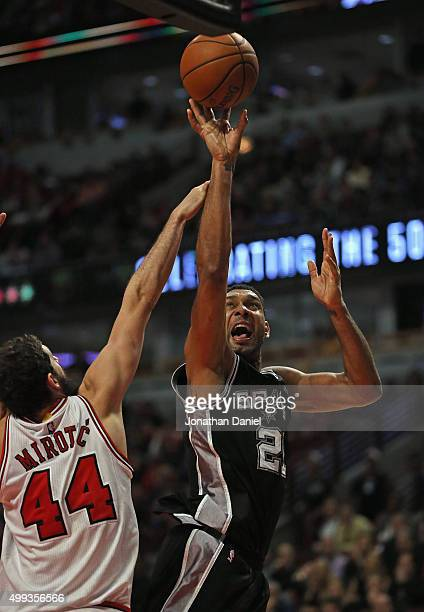 Tim Duncan of the San Antonio Spurs shoots over Nikola Mirotic of the Chicago Bulls at the United Center on November 30 2015 in Chicago Illinois The...