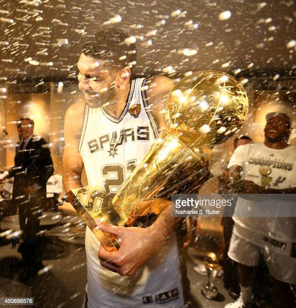 Tim Duncan of the San Antonio Spurs showered with champagne in the locker room with the Larry O'Brien Trophy after winning the 2014 NBA Finals at ATT...