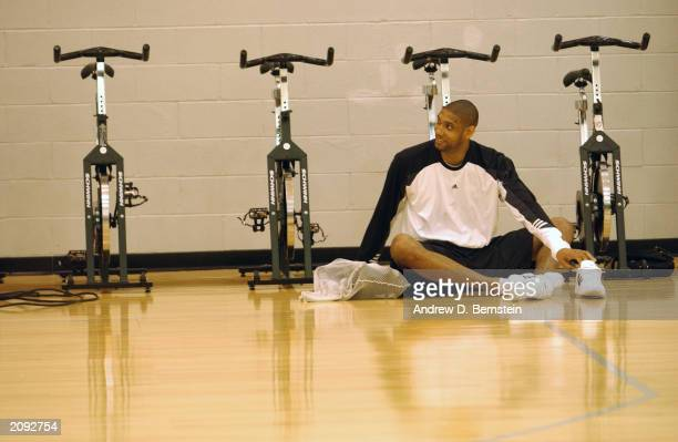 Tim Duncan of the San Antonio Spurs stretches on the court during practice prior to Game Four of the 2003 NBA Finals against the New Jersey Nets at...