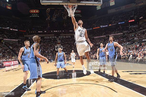 Tim Duncan of the San Antonio Spurs takes the ball to the basket between Carlos Boozer and Mehmet Okur of the Utah Jazz in Game Two of the Western...