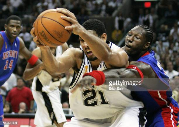 Tim Duncan of the San Antonio Spurs tries to keep the ball away from the defense of Ben Wallace of the Detroit Pistons in Game seven of the 2005 NBA...