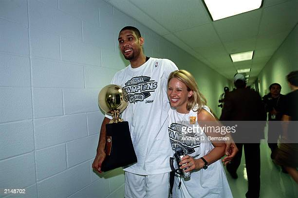Tim Duncan of the San Antonio Spurs walks in the hallway along with his wife after winning game six of the 2003 NBA Finals to win the championship on...