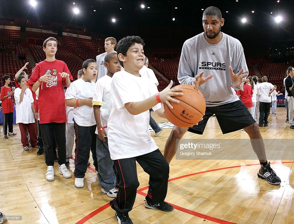 Tim Duncan #21 of the San Antonio Spurs works with kids at a NBA Cares / Special Olympics clinic during the NBA Europe Live Tour presented by EA Sports on October 7, 2006 in Paris, France.