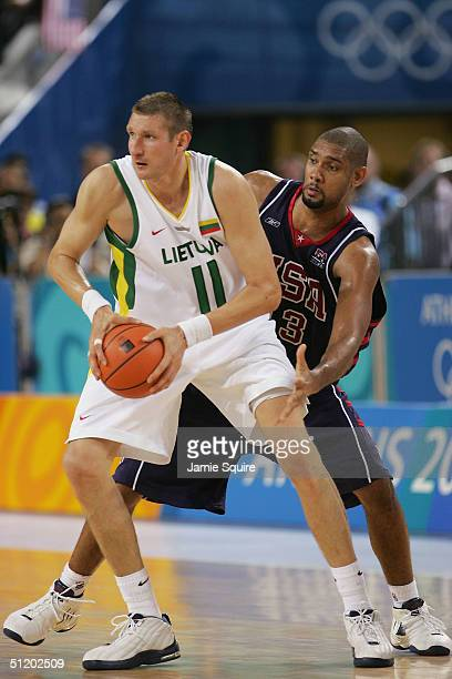 Tim Duncan of the United States defends Eurelijus Zukauskas of Lithuania in a men's basketball preliminary game on August 21, 2004 during the Athens...