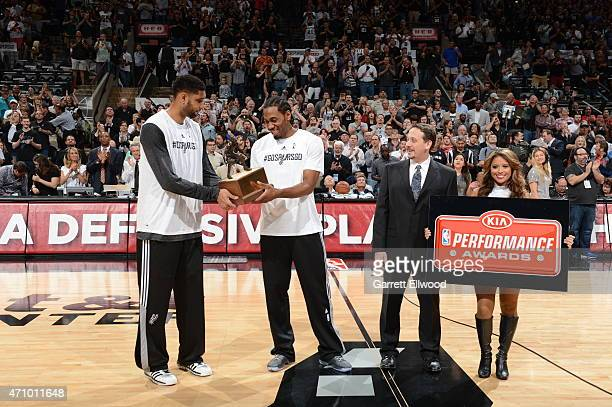 Tim Duncan presents Kawhi Leonard of the San Antonio Spurs with the Kia Defensive Player of the Year Award before the game against the Los Angeles...