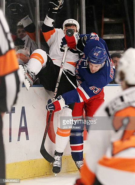 Tim Erixon of the New York Rangers checks Zac Rinaldo of the Philadelphia Flyers in the first period on December 23 2011 at Madison Square Garden in...
