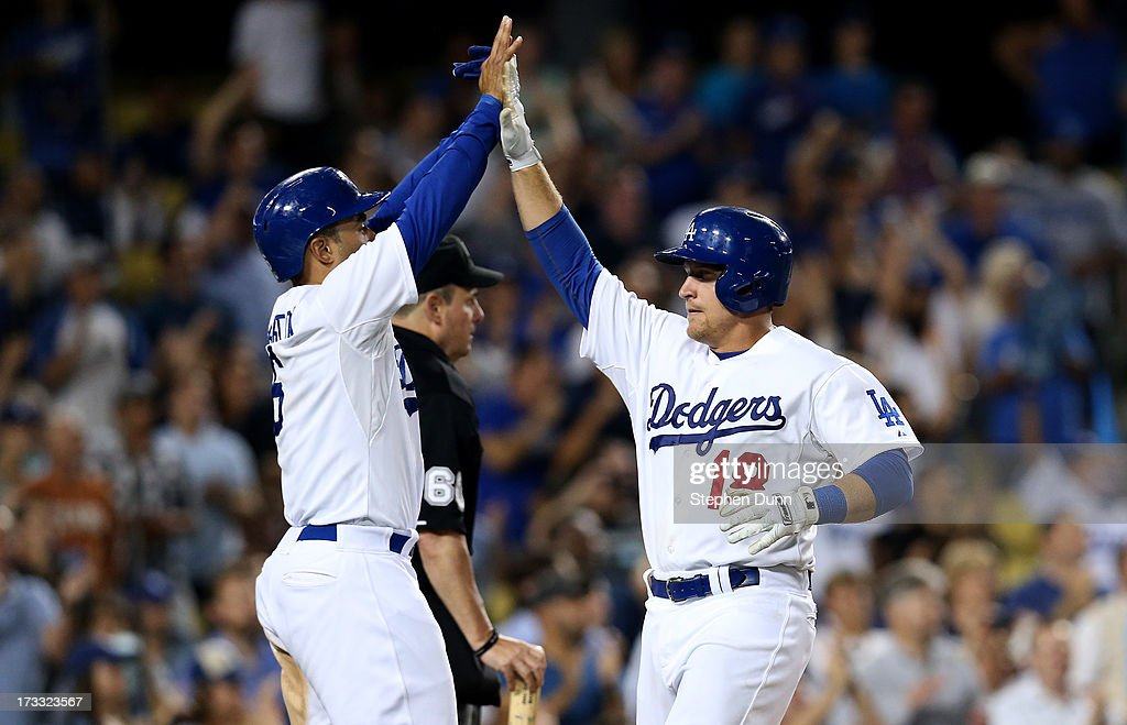 Tim Federowicz #18 and Jerry Hairston Jr. #6 of the Los Angeles Dodgers celebrate after both score on mark Ellis' two rn double in the eighth innng against the Colorado Rockies at Dodger Stadium on July 11, 2013 in Los Angeles, California.