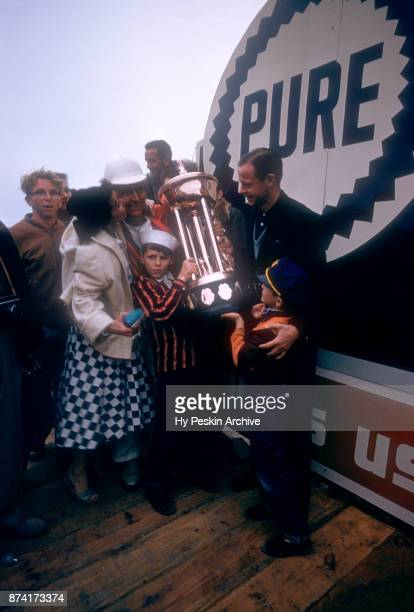 Tim Flock driver of the 1955 Chrysler celebrates with his family and the trophy after winning the Daytona Beach and Road Course on February 26 1956...