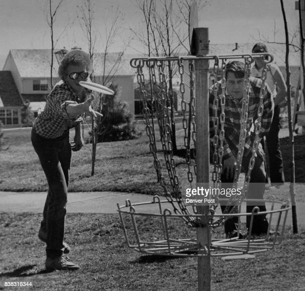 Tim Forbriger putts for a baskettype hole while Veeder Dorn watches from behind chains during Disc Golf Tournament Saturday at KenCaryl Ranch...