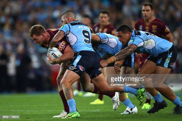 Tim Glasby of the Maroons is tackled during game two of the State Of Origin series between the New South Wales Blues and the Queensland Maroons at...