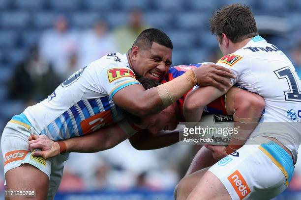Tim Glasby of the Newcastle Knights is tackled by the Titans defence during the round 24 NRL match between the Newcastle Knights and the Gold Coast...