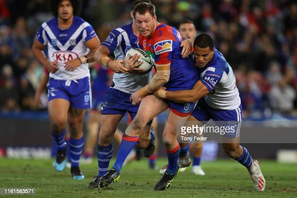 Tim Glasby of the Newcastle Knights is tackled during the round 17 NRL match between the Newcastle Knights and the Canterbury Bulldogs at McDonald...