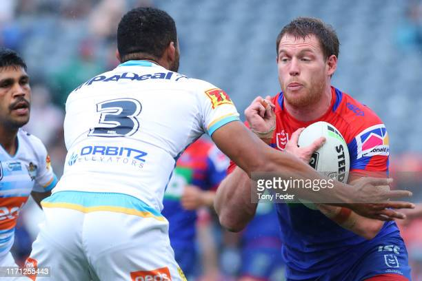Tim Glasby of the Newcastle Knights is tackled during the round 24 NRL match between the Newcastle Knights and the Gold Coast Titans at McDonald...