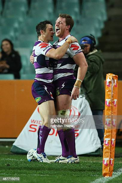 Tim Glasby of the Storm celebrates with team mate Cooper Cronk after scoring a try during the NRL qualifying final match between the Sydney Roosters...