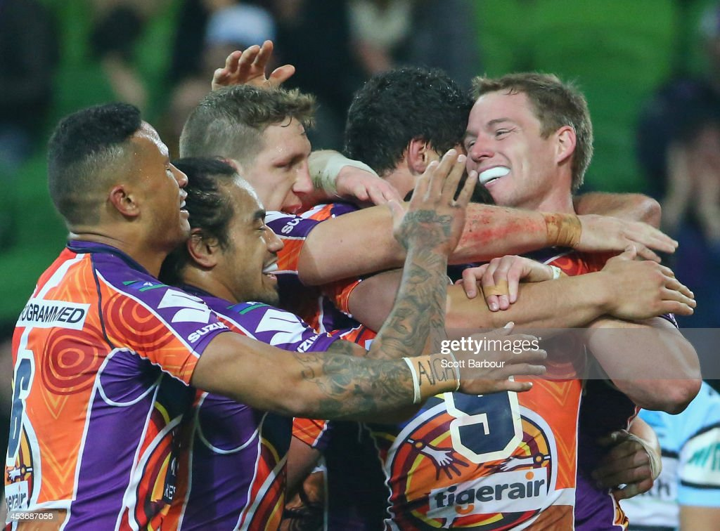 Tim Glasby (R) of the Storm is congratulated after scoring a try during the round 23 NRL match between the Melbourne Storm and the Cronulla Sharks at AAMI Park on August 16, 2014 in Melbourne, Australia.