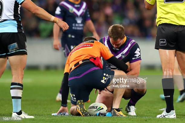 Tim Glasby of the Storm is seen by a trainer during the NRL Preliminary Final match between the Melbourne Storm and the Cronulla Sharks at AAMI Park...