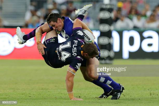 Tim Glasby of the Storm is tackled by Josh Jackson of the Bulldogs during the round one NRL match between the Canterbury Bulldogs and the Melbourne...