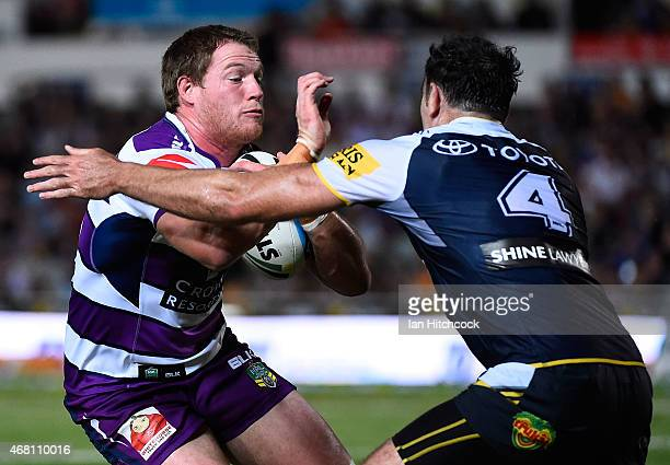 Tim Glasby of the Storm is tackled by Kane Linnett of the Cowboys during the round four NRL match between the North Queensland Cowboys and the...