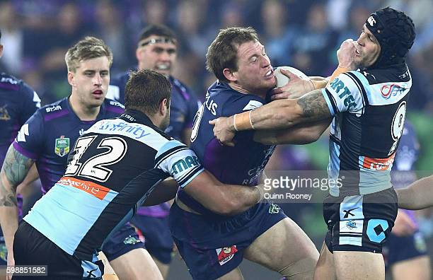 Tim Glasby of the Storm is tackled by Michael Ennis of the Sharks during the round 26 NRL match between the Melbourne Storm and the Cronulla Sharks...