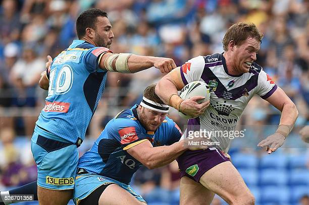 Tim Glasby of the Storm is tackled during the round nine NRL match between the Gold Coast Titans and the Melbourne Storm on May 1 2016 in Gold Coast...