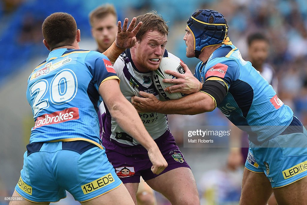 Tim Glasby of the Storm is tackled during the round nine NRL match between the Gold Coast Titans and the Melbourne Storm on May 1, 2016 in Gold Coast, Australia.