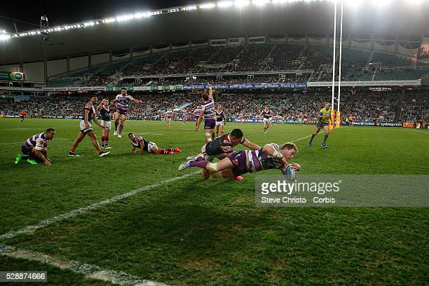 Tim Glasby of the Storm scores the winning try while being tackled by the Rooster's Roger TuivasaSheck during the Qualifying Final match between...