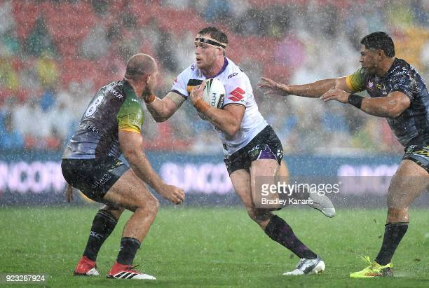 Tim Glasby of the Storm takes on the defence during the NRL trial match and Jonathan Thurston/Cameron Smith Testimonial match between the Melbourne...