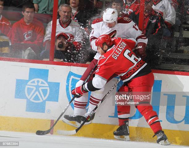 Tim Gleason of the Carolina Hurricanes collides into the boards with Radim Vrbata of the Phoenix Coyotes during a NHL game on March 13, 2010 at RBC...