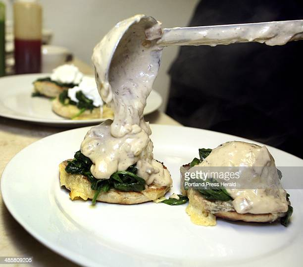 The smoky bacon cream is poured over the poached eggs Porthole Executive Chef Paul Dyer prepares eggs florentine with a smoky bacon cream at the...