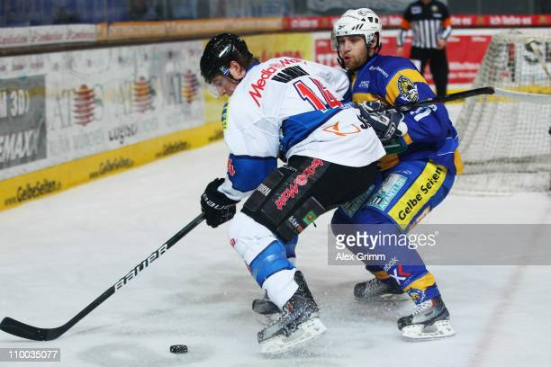 Tim Hambly of Ingolstadt is challenged by Kyle Helms of Muenchen during the DEL match between EHC Muenchen and ERC Ingolstadt at Olympia Eishalle on...