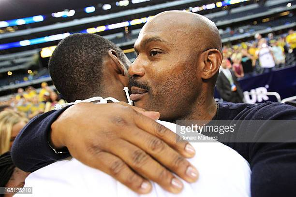 Tim Hardaway Jr #10 of the Michigan Wolverines celebrates with his father Tim Hardaway after their 79 to 59 win over the Florida Gators during the...