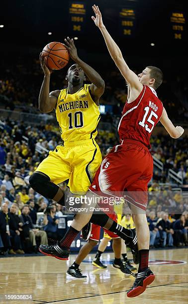 Tim Hardaway Jr #10 of the Michigan Wolverines gets a first half shot off around the defense of Scott Wood of the North Carolina State Wolfpack at...