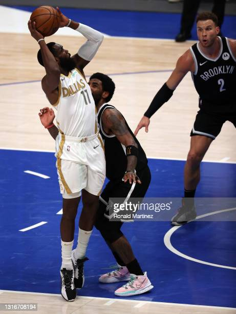 Tim Hardaway Jr. #11 of the Dallas Mavericks takes a shot against Kyrie Irving of the Brooklyn Nets in the third quarter at American Airlines Center...