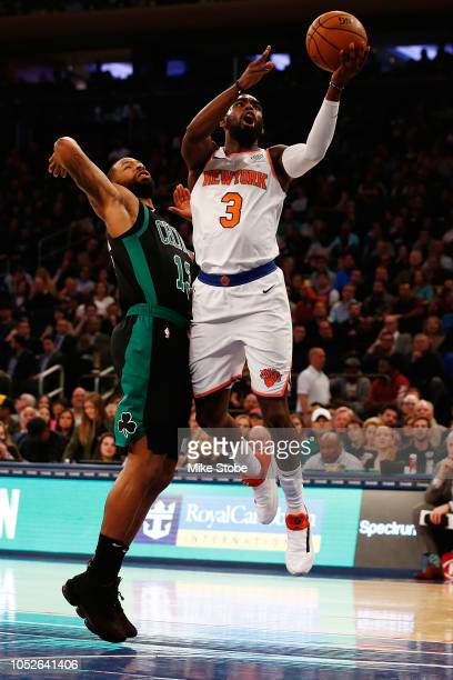 Tim Hardaway Jr #3 of the New York Knicks drives towards the net against Marcus Morris of the Boston Celtics at Madison Square Garden on October 20...