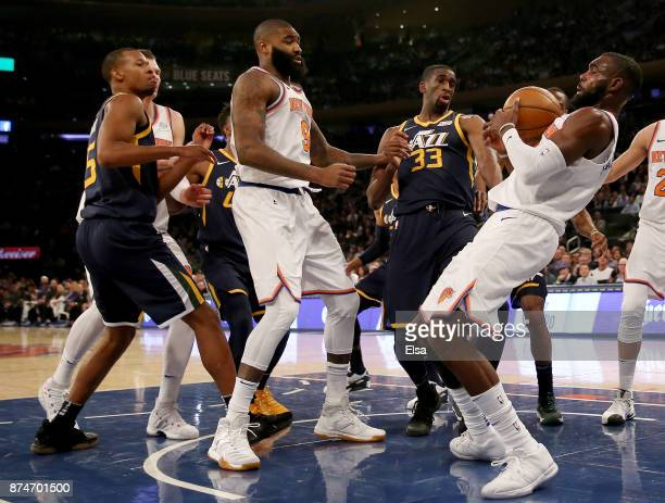 Tim Hardaway Jr #3 of the New York Knicks grabs the rebound before teammate Kyle O'Quinn of the New York Knicks as Rodney Hood and Ekpe Udoh of the...