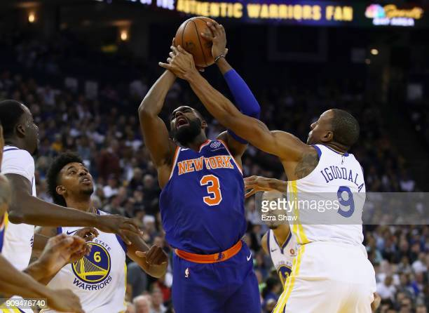 Tim Hardaway Jr #3 of the New York Knicks is fouled by Andre Iguodala of the Golden State Warriors at ORACLE Arena on January 23 2018 in Oakland...