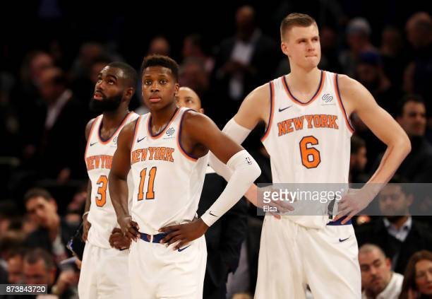 Tim Hardaway Jr #3Frank Ntilikina and Kristaps Porzingis of the New York Knicks react in the fourth quarter against the Cleveland Cavaliers at...