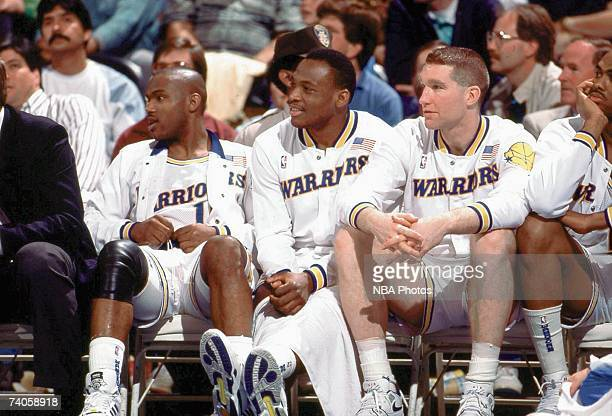 Tim Hardaway Mitch Richmond and Chris Mullin of the Golden State Warriors sit on the bench during a game played in 1989 at the OaklandAlameda...