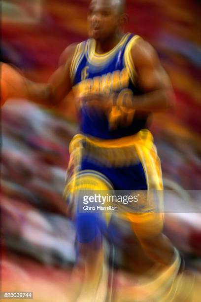 Tim Hardaway of the Golden State Warriors dribbles the ball up court against the Atlanta Hawks at the Omni Coliseum in Atlanta Georgia circa 1992...