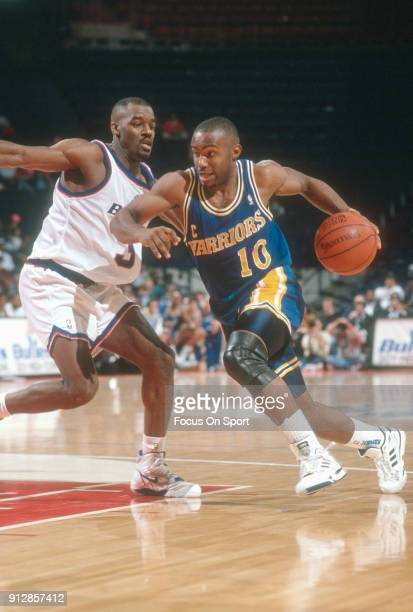 Tim Hardaway of the Golden State Warriors drives on Haywoode Workman 33 of the Washington Bullets during an NBA basketball game circa 1990 at the...