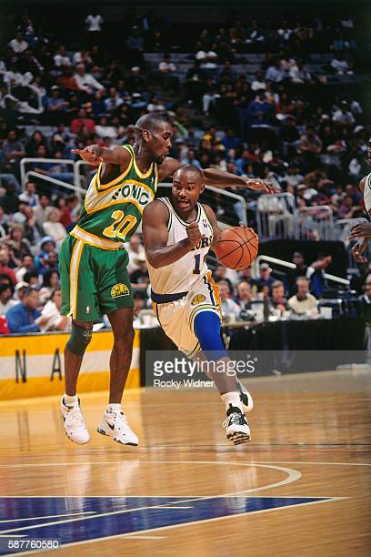 Tim Hardaway of the Golden State Warriors drives to the basket against the Seattle SuperSonics circa 1996 at OaklandAlameda County Coliseum Arena in...
