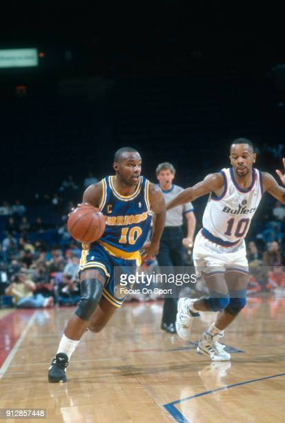 Tim Hardaway of the Golden State Warriors drives toward the basket on Michael Adams of the Washington Bullets during an NBA basketball game circa...