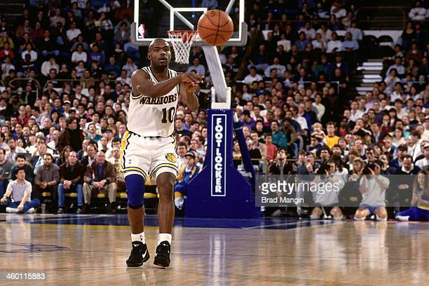 Tim Hardaway of the Golden State Warriors passes against the Phoenix Suns during a game played in 1993 at the OaklandAlameda County Coliseum Arena in...