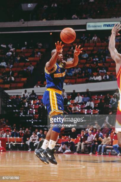 Tim Hardaway of the Golden State Warriors passes the ball against the Atlanta Hawks during a game played circa 1990 at the Omni in Atlanta Georgia...