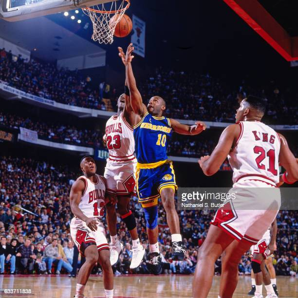 Tim Hardaway of the Golden State Warriors shoots against Michael Jordan of the Chicago Bulls during a game played circa 1993 at Chicago Stadium in...