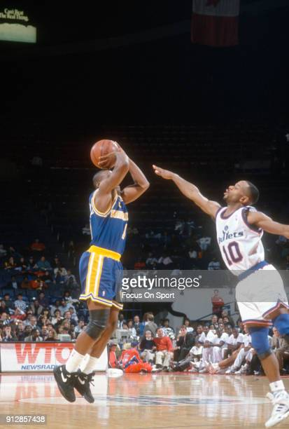 Tim Hardaway of the Golden State Warriors shoots over Michael Adams of the Washington Bullets during an NBA basketball game circa 1992 at the Capital...