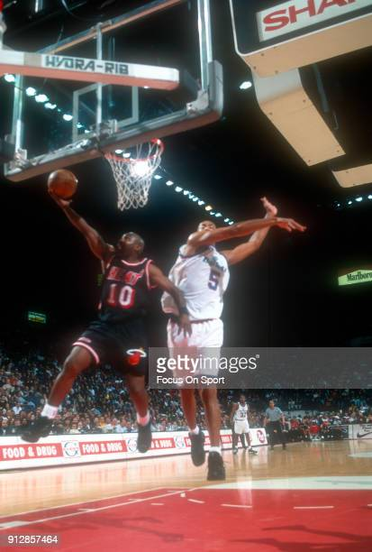 Tim Hardaway of the Miami Heat goes in for a layup in front of Juwan Howard of the Washington Bullets during an NBA basketball game circa 1997 at the...